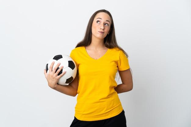 Женщина молодой футболист над изолированным белым и глядя вверх