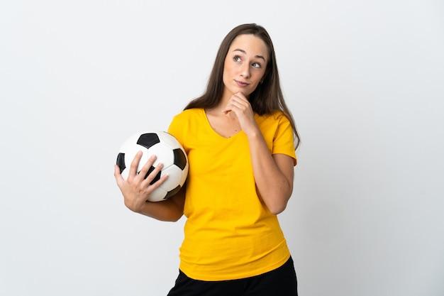 Женщина молодой футболист на изолированном белом фоне и глядя вверх
