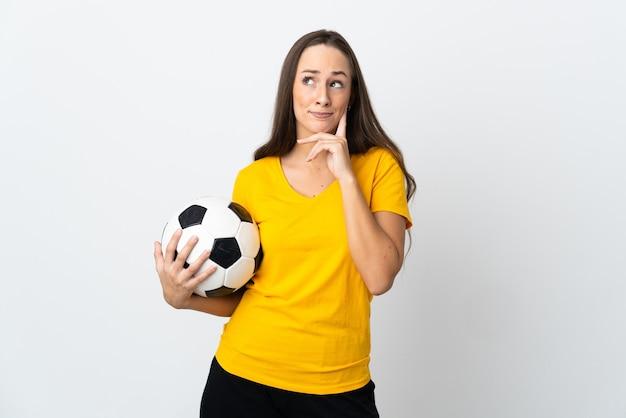 Женщина молодой футболист на изолированном белом фоне с сомнениями и мышлением