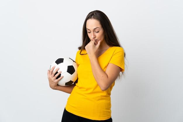 Женщина молодой футболист на изолированном белом фоне, сомневаясь
