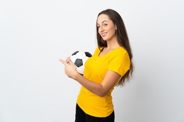 Женщина молодой футболист на изолированном белом фоне, указывая назад