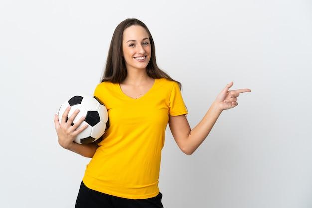 Молодая женщина-футболист на изолированном белом фоне, указывая пальцем в сторону