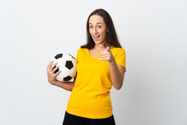 Молодой футболист женщина на изолированном белом фоне удивлен и указывает фронт