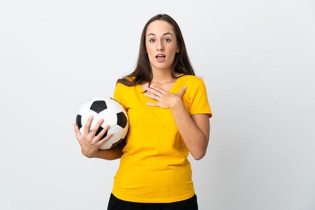 Молодая женщина-футболист на изолированном белом фоне удивлена и шокирована, глядя вправо