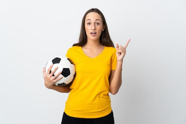 Молодая женщина-футболист на изолированном белом фоне думает о идее, указывая пальцем вверх