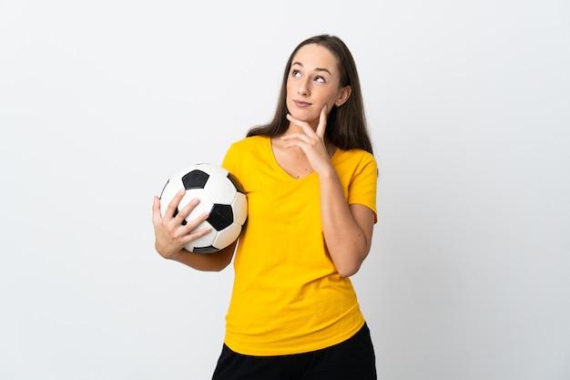 Женщина молодой футболист на изолированном белом фоне, думая об идее, глядя вверх