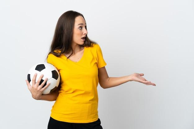 Молодая женщина-футболист на изолированном белом фоне с удивленным выражением лица, глядя в сторону