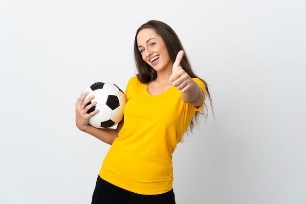 좋은 일이 일어났기 때문에 엄지 손가락으로 격리 된 흰색 배경 위에 젊은 축구 선수 여자