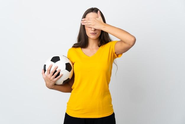 Молодая женщина футболиста над изолированными белыми заволакивающими глазами руками. не хочу что-то видеть