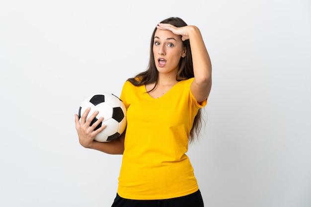 Молодая женщина-футболист над изолированным белым делает неожиданный жест, глядя в сторону