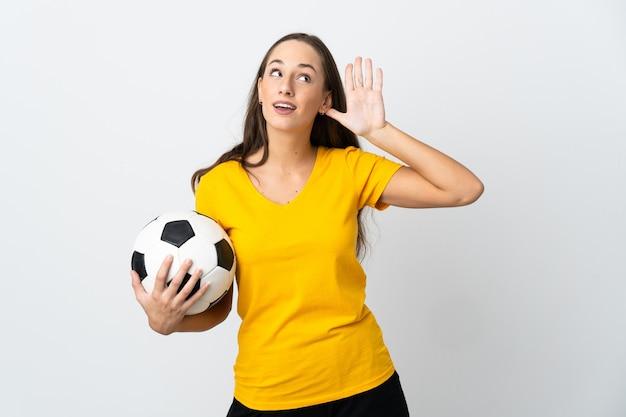 Молодой футболист женщина над изолированным белым слушает что-то, положив руку на ухо