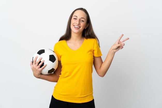 Женщина молодого футболиста над изолированной белой улыбкой и показом знака победы