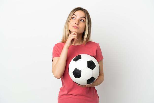 Женщина молодой футболист над изолированной белой стеной и глядя вверх