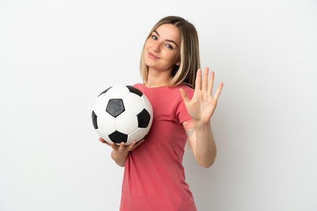 Молодой футболист женщина над изолированной белой стеной, считая пять пальцами