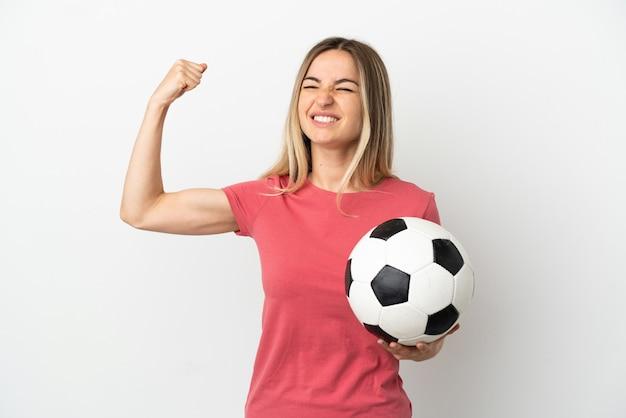 Молодая женщина-футболист над изолированной белой стеной делает сильный жест
