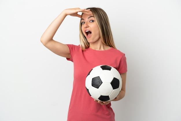 Молодая женщина-футболист над изолированной белой стеной делает неожиданный жест, глядя в сторону