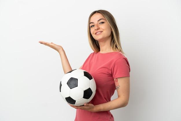 외진 흰 벽 너머로 젊은 축구 선수 여성이 초대하기 위해 손을 옆으로 뻗고 있다