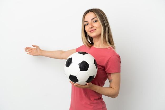Молодой футболист женщина над изолированной белой стеной, протягивая руки в сторону, чтобы пригласить приехать