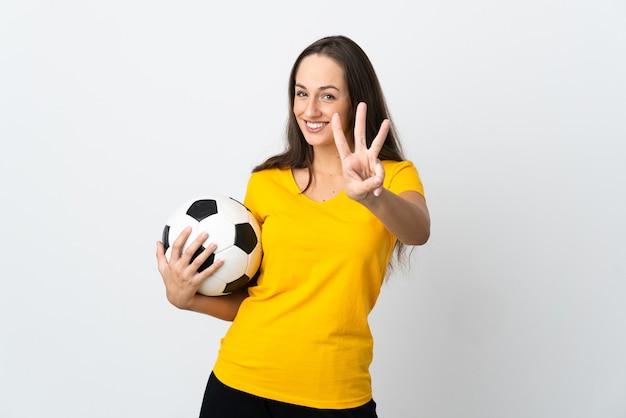 격리 된 흰 벽에 젊은 축구 선수 여자 행복 하 고 손가락으로 세 세