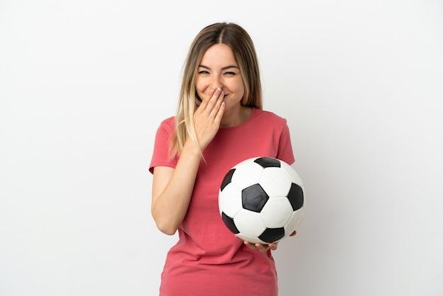 Молодая женщина-футболист над изолированной белой стеной счастлива и улыбается, прикрывая рот рукой