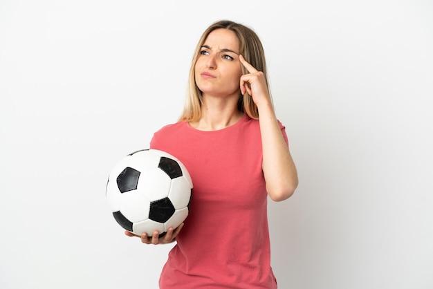 Молодой футболист женщина над изолированной белой стеной, сомневаясь и думая