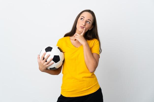 Женщина молодой футболист над изолированной белой стеной, сомневаясь, глядя вверх