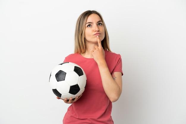 Молодой футболист женщина над изолированной белой стеной, сомневаясь, глядя вверх