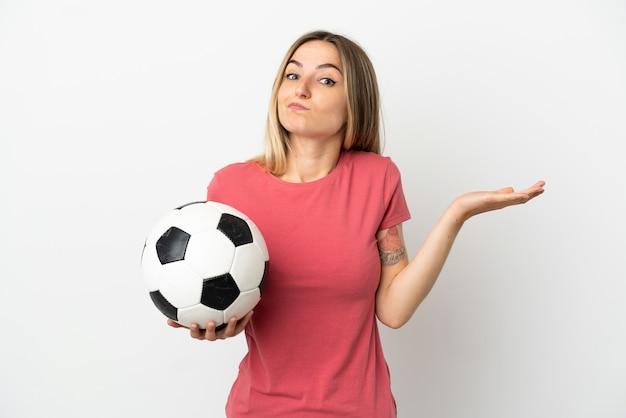 Молодая женщина-футболист над изолированной белой стеной сомневается, поднимая руки