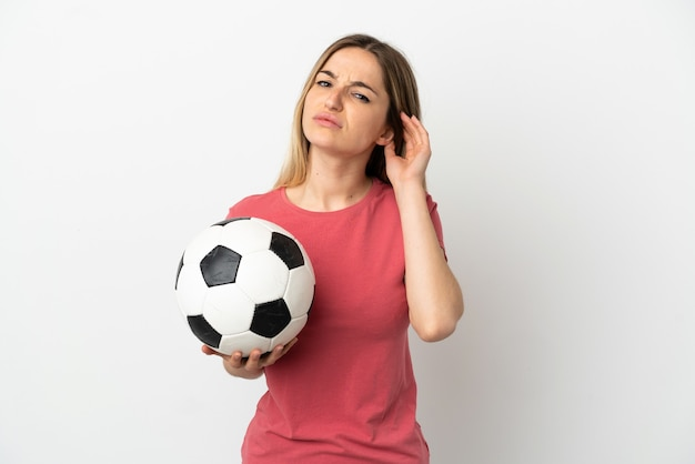 Женщина молодой футболист над изолированной белой стеной, сомневаясь