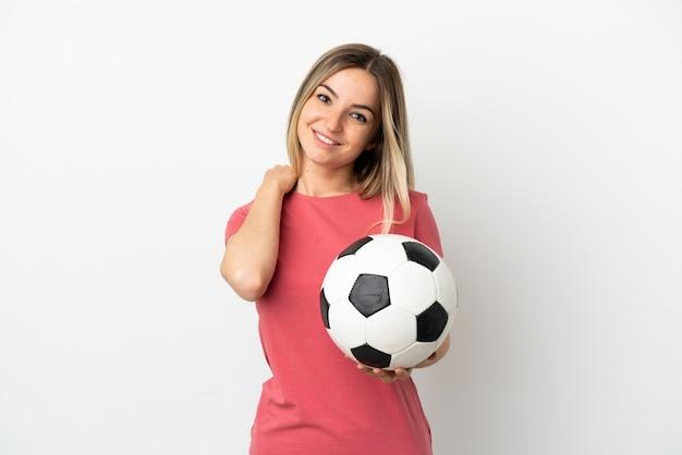 笑っている孤立した白い壁の上の若いサッカー選手の女性