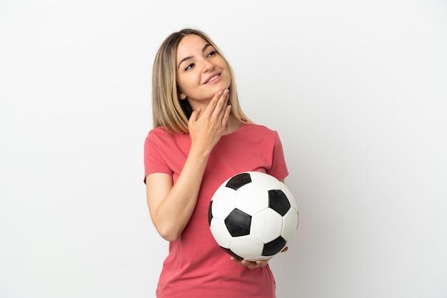Молодая женщина-футболист над изолированной белой стеной смотрит вверх, улыбаясь