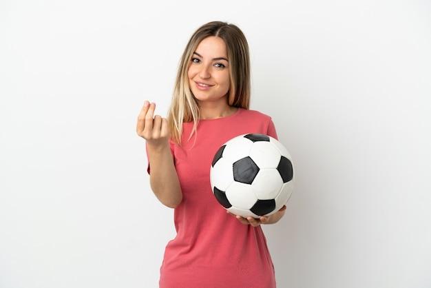 Молодая женщина-футболист над изолированной белой стеной делает денежный жест