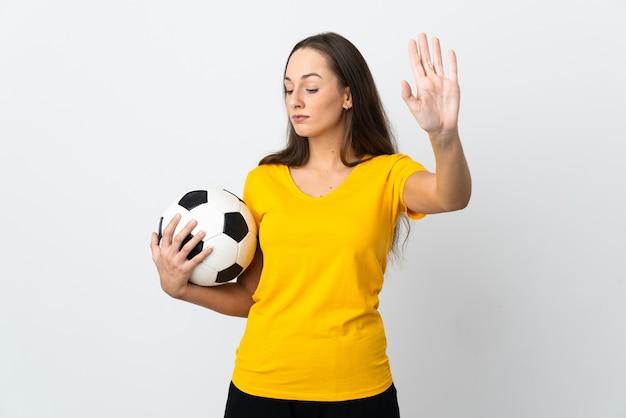 Молодая женщина-футболист над изолированной белой стеной делает стоп-жест и разочарована