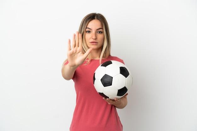 Молодая женщина-футболист над изолированной белой стеной делает стоп-жест