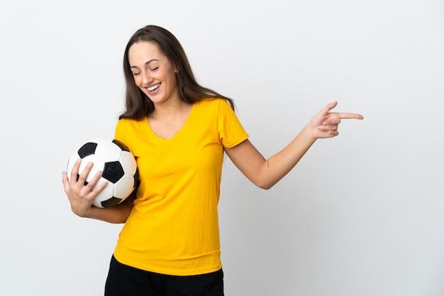Молодая женщина-футболист над изолированной белой стеной, указывая пальцем в сторону и представляя продукт