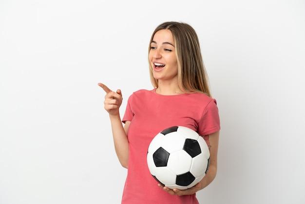외진 흰 벽 너머로 손가락을 옆으로 가리키고 제품을 제시하는 젊은 축구 선수 여성