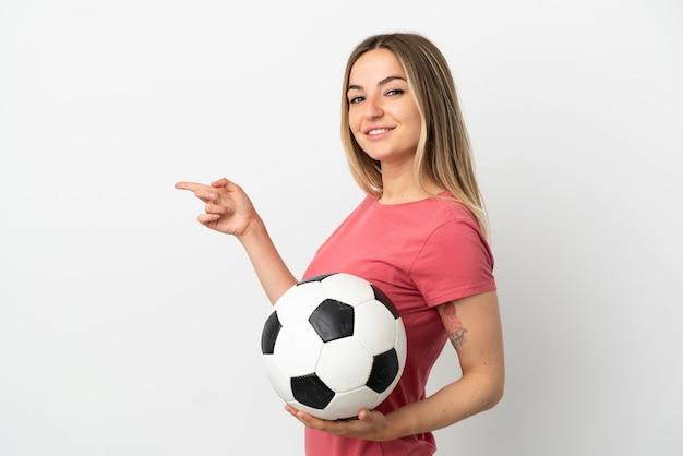 Молодая женщина-футболист над изолированной белой стеной, указывая пальцем в сторону