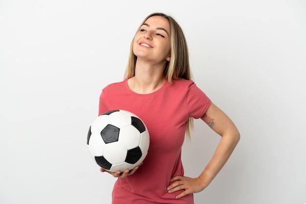고립 된 흰 벽에 젊은 축구 선수 여자 엉덩이에 팔을 포즈와 미소