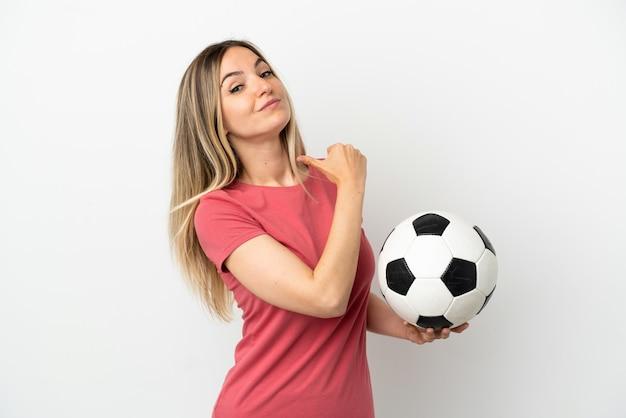 Женщина молодого футболиста над изолированной белой стеной гордая и самодовольная