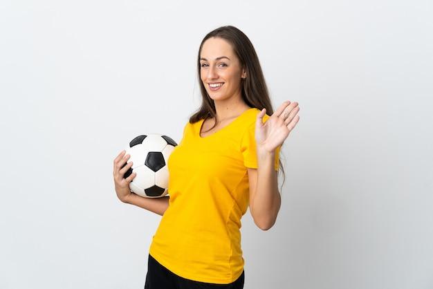 Молодой футболист женщина над изолированной белой стеной, салютуя рукой с счастливым выражением лица