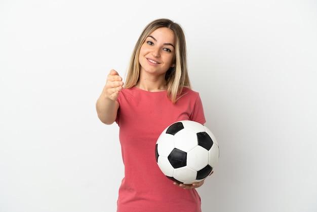 Молодой футболист женщина над изолированной белой стеной, пожимая руку для заключения хорошей сделки