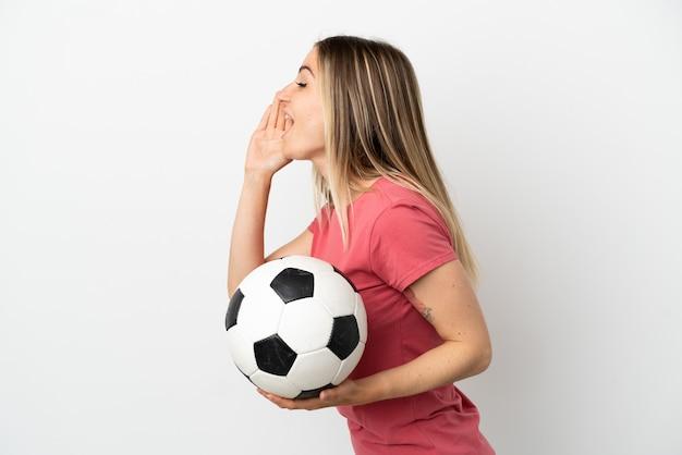 Молодой футболист женщина над изолированной белой стеной кричит с широко открытым ртом в сторону