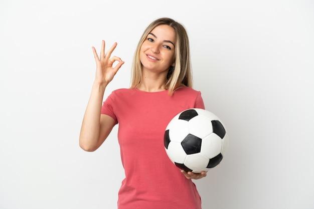 Молодой футболист женщина над изолированной белой стеной показывает знак ок с пальцами