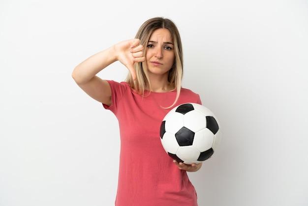 Женщина молодого футболиста над изолированной белой стеной показывает большой палец вниз с отрицательным выражением лица