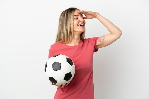 Молодой футболист женщина над изолированной белой стеной, много улыбаясь