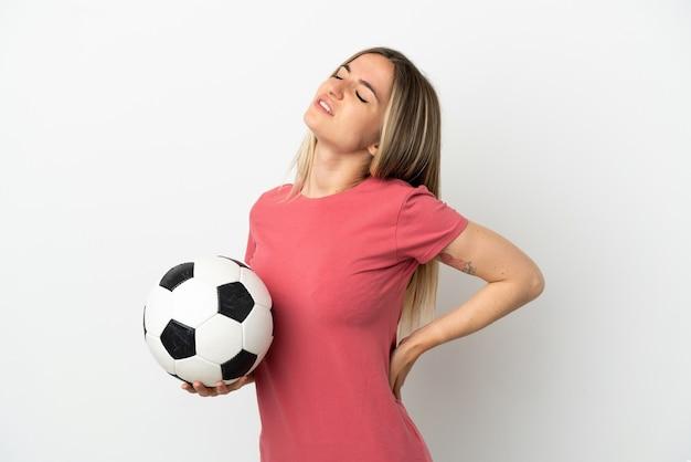 Молодая женщина-футболист над изолированной белой стеной страдает от боли в спине за то, что приложила усилие