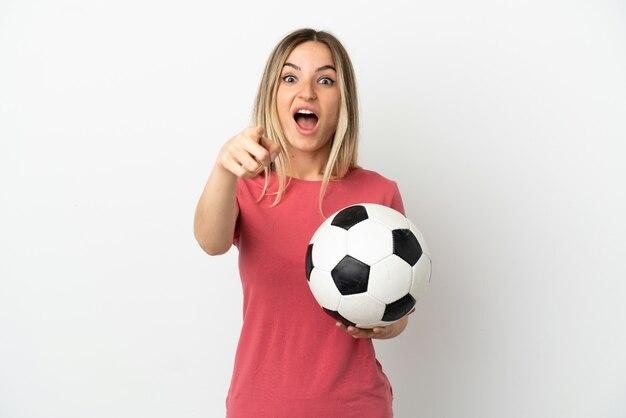 격리 된 흰 벽에 젊은 축구 선수 여자 놀고 앞을 가리키는