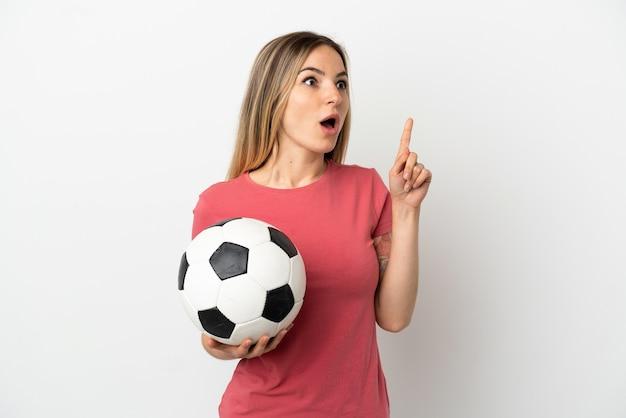 Молодая женщина-футболист над изолированной белой стеной думает об идее, указывая пальцем вверх