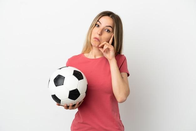 Молодой футболист женщина над изолированной белой стеной, думая об идее