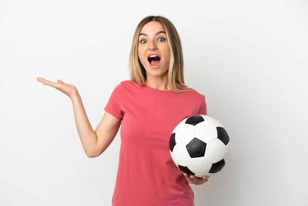 Молодой футболист женщина над изолированной белой стеной с шокированным выражением лица